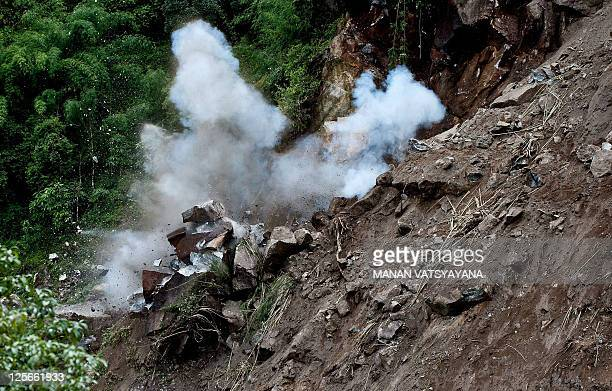 Indian Border Road Organisation personnel use an explosive device to clear a landslide at Phengla on the outskirts of Gangtok on September 20 after a...