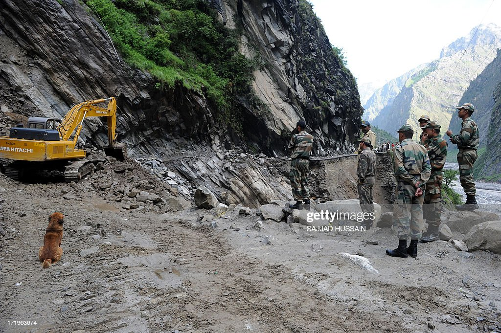 Indian Border Roads Organisation (BRO) workers clear a landslide across the road caused by overnight rains as Indian army soldiers look on at Govindghat following flash floods in northern Uttarakhand state, on June 30, 2013. Some 3,000 tourists and pilgrims remain missing in India's flood-ravaged north two weeks after the tragedy, but it is unclear how many of those have been killed, a top state official said June 30.