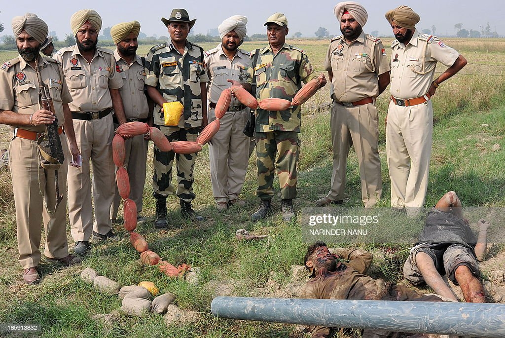 Indian Border Security Force (BSF) and Punjab Police personnel hold heroin packets and stand near alleged Pakistani smugglers killed during an overnight operation at the India-Pakistan Border Mullakot, around 45kms from Amritsar on October 26, 2013. The BSF said that personnel recovered the 24 packets of heroin, one AK47 Rifle, and two pistols from the alleged smugglers.