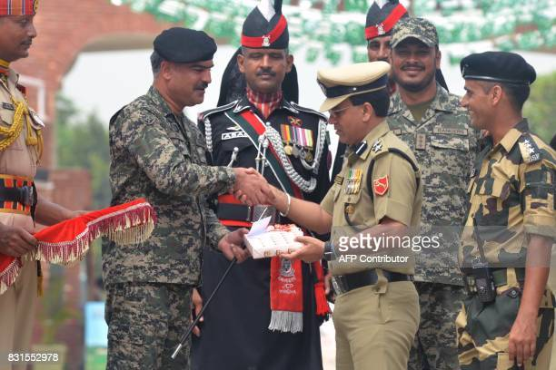Indian Border Security Force Commandant Sudeep presents sweets as he shake hand with the Pakistani Wing Commander Bilal during a ceremony to...