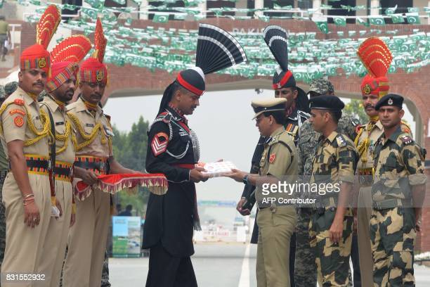 Indian Border Security Force Commandant Sudeep presents sweets to Pakistani Ranger during a ceremony to celebrate India's Independence Day at the...