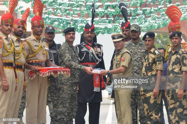 Indian Border Security Force Commandant Sudeep presents sweets to Pakistani Wing Commander Bilal during a ceremony to celebrate India's Independence...
