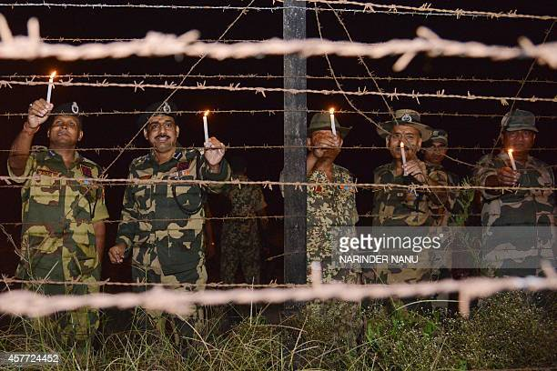 Indian Border Security Force Deputy Inspector General M F Farooqui along with BSF personnel place candles along the fence as they celebrate Diwali at...