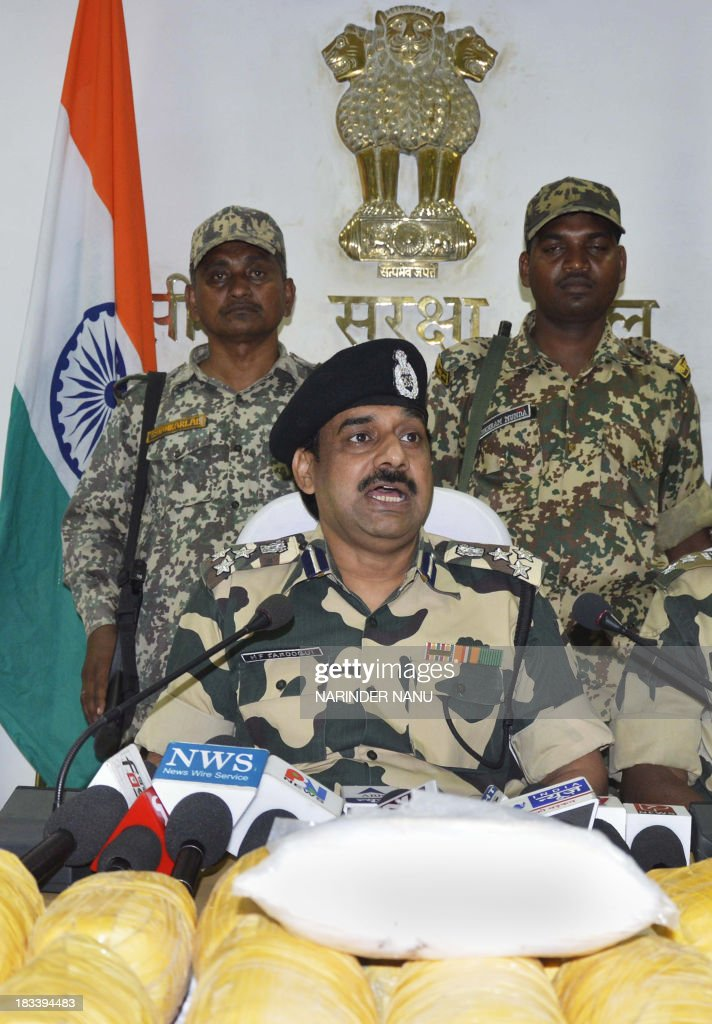 Indian Border Security Force (BSF) Deputy Inspector General (DIG), MF Farooqui, speaks during a press conference, alongside packets of confiscated heroin recovered near the India-Pakistan border, at the BSF head quarters in Khasa, 15 kilometres (9 miles) from Amritsar on October 6, 2013. Seventeen packets of heroin were recovered near the India-Pakistan border outpost Pulmoran, after the narcotics were allegedly smuggled into India from Pakistan, officials said.