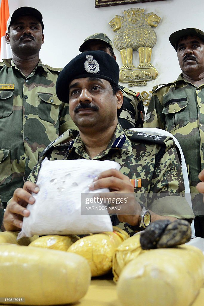 Indian Border Security Force (BSF) Deputy Inspector General (DIG), MF Farooqui (C) and other BSF officers pose with 11 kilogrammes (24 pounds) of confiscated heroin recovered near the border of India and Pakistan, at the BSF head quarters in Khasa, some 15 kilometres from Amritsar on September 2, 2013. Eleven packets of heroin were recovered near the India and Pakistan ,Border Out Post Amar, after the narcotics were allegedly smuggled into the country from neighbouring Pakistan, officials said. AFP PHOTO/ NARINDER NANU
