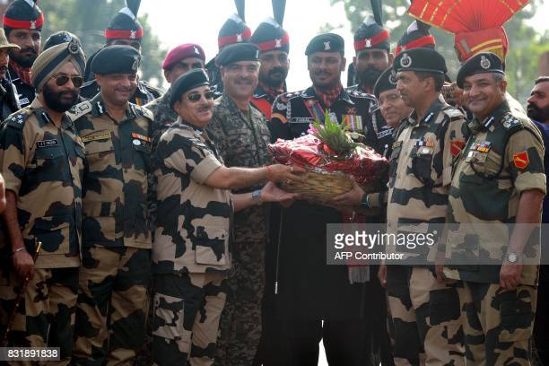 Indian Border Security Force Director General K K Sharma BSF Deputy Inspector General JS Oberoi BSF Commandant Sudeep presents sweets and fruits to...
