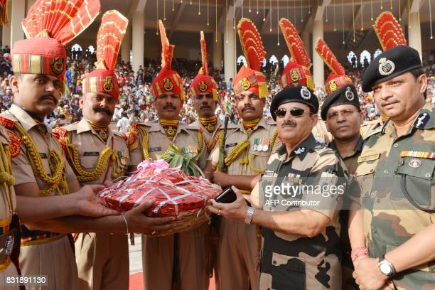 Indian Border Security Force Director General K K Sharma BSF Commandant Sudeep presents sweets and fruits to the BSF Soldiers during a ceremony to...