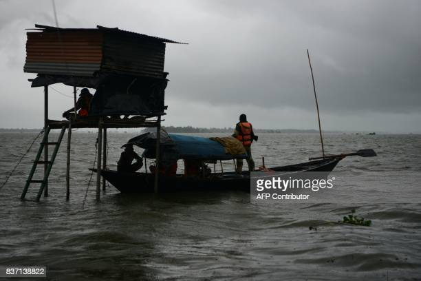 Indian Border Security Force personal patrols in a country boat near a watch tower at the flooded IndiaBangladesh border area in Jagjiwanpur BOP near...