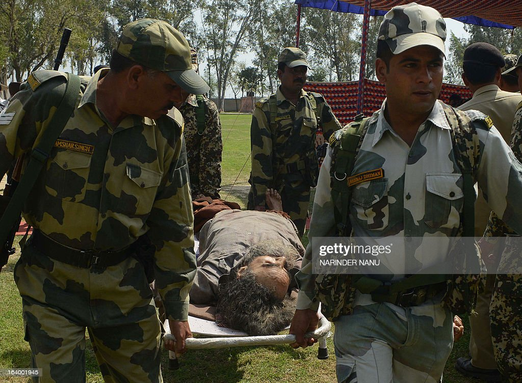 Indian Border Security Force (BSF) personnel carry the dead body of an alleged Indian smuggler, killed during an overnight operation, to be displayed to journalists at the BSF headquarters in Khem Karan, about 65 kms from Amritsar, on March 19,2013. BSF personnel recovered ten packets of heroin, a pistol with four rounds of ammunition, and a mobile phone from alleged Indian smuggler identified as Kuldeep Singh, who was killed during an overnight operation near the Harbhajan post along the Indian Pakistan-border.