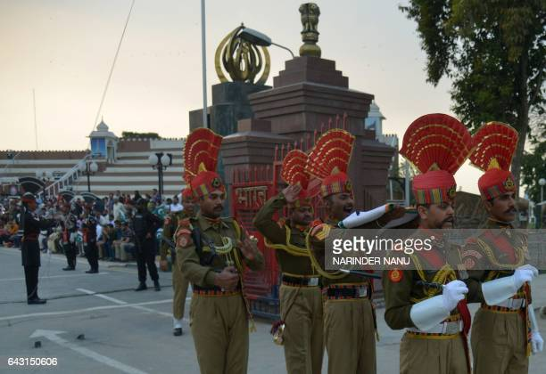 Indian Border Security Force personnel carry the national flag after performing during the daily beating of the retreat ceremony on the IndiaPakistan...