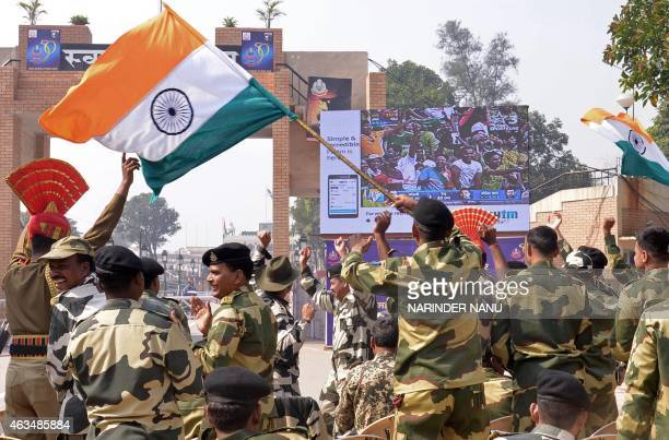 Indian Border Security Force personnel celebrate as they watch a live broadcast of the Cricket World Cup match between Indian and Pakistan at the...