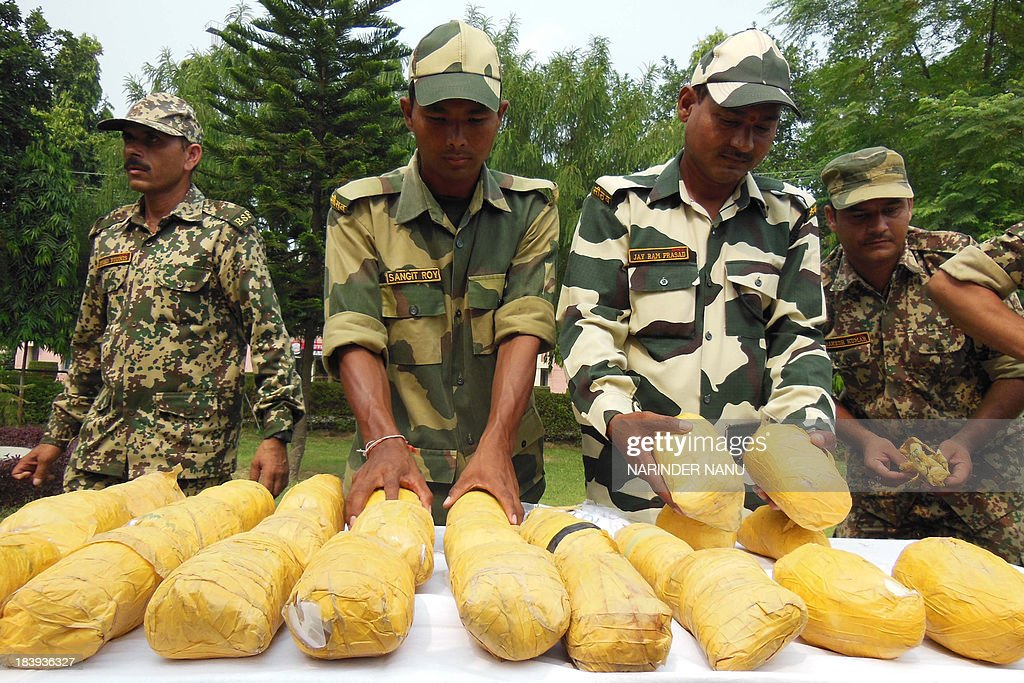 Indian Border Security Force (BSF) personnel display 26 kgs of confiscated heroin, recovered near the India-Pakistan border, during a press conference at the BSF headquarters in Khasa, 15 kilometres (9 miles) from Amritsar on October 10, 2013. 26 packets of heroin were recovered near the India-Pakistan border outpost Rajatal, after the narcotics were allegedly smuggled into India from Pakistan, officials said.