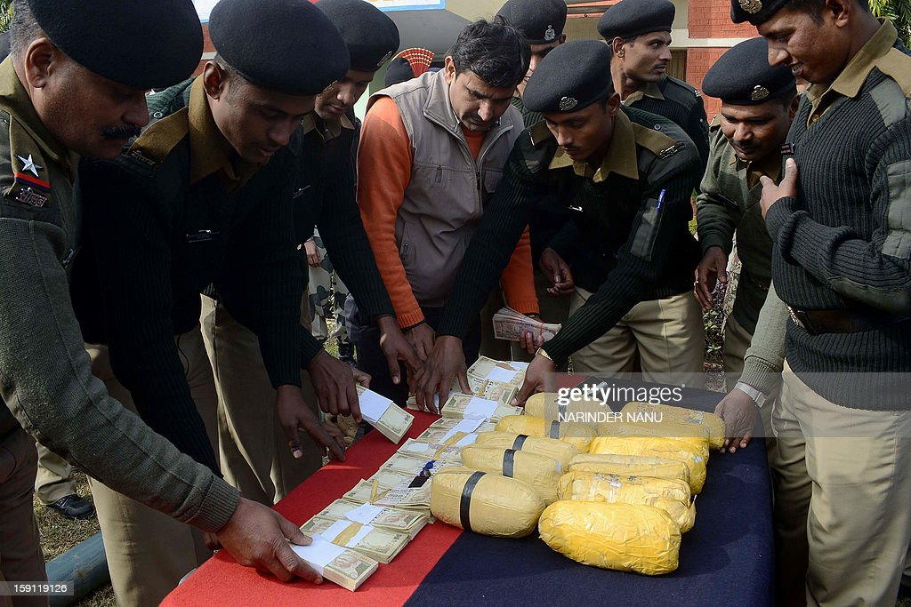 Indian Border Security Force (BSF) personnel display eleven packets of confiscated heroin and counterfeit Indian rupee notes during a press conference held close to the India-Pakistan Border at BSF headquarters in Amarkot, some 55 kms from Amritsar on January 8, 2013. Indian Border Security Force (BSF) Commander Madan Lal said that BSF personnel recovered eleven packets of heroin and 11,90,500 fake Indian currency from an alleged three Pakistani smugglers who ran back to Pakistan under the cover of heavy fog.