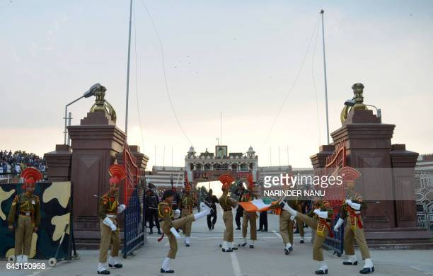Indian Border Security Force personnel fold the national flag as they perform during the daily beating of the retreat ceremony on the IndiaPakistan...
