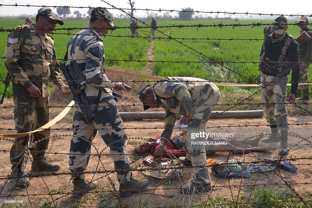 Indian Border Security Force (BSF) personnel inspect the body of one of two alleged Pakistani smugglers killed near a checkpoint at Mehdipur near the India-Pakistan border, about 70 kms from Amritsar, on February 7, 2016. BSF personnel killed two Pakistani and two Indian smugglers, officials said, as authorities also recovered some 10 packets of heroin along with fire arms, cash and a knife. AFP PHOTO/NARINDER NANU / AFP / NARINDER NANU