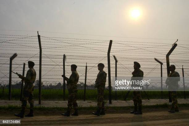 Indian Border Security Force personnel patrol along a fence at the IndiaPakistan border at Wagah some 35kms from Amritsar on February 20 2017 / AFP /...