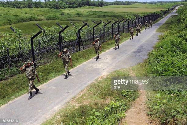 Indian Border Security Force personnel patrol alongside a barbed wire fence which marks the border with Bangladesh at Patriduwar some 75kms south of...