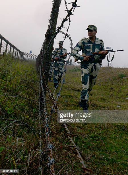 Indian Border Security Force personnel patrol the border with Bangladesh near the Fulbari Border post some 20 kms from Siliguri on January 4 2014...