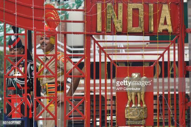 Indian Border Security Force soldier and Pakistani ranger stand guard during a ceremony to celebrate India's Independence Day at the IndiaPakistan...
