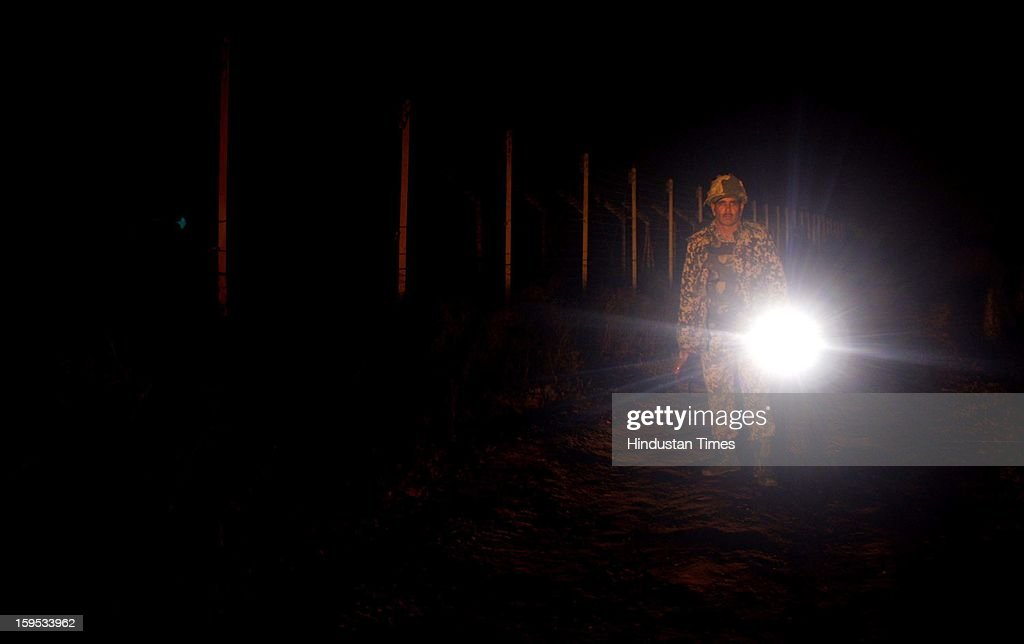 Indian Border Security Force (BSF) soldier stand guard during night patrol near the fenced border with Pakistan at Abdullian on January 14, 2013 about 40 kilometers from Jammu, India. A Flag meeting was held between the Pakistani and Indian army commanders at LoC at the Chakan Da Bagh, in Poonch, 245 kilometers from Jammu to defuse the tension which escalated after Pakistani troops killed two Indian soldiers.