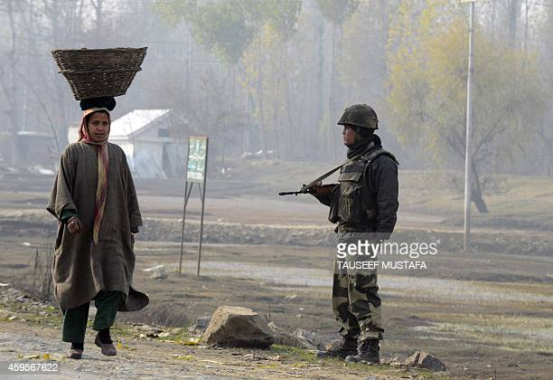 Indian Border Security Force soldier stands guard as Kashmiri woman carries willow basket on her head near a polling station in Saderkote on November...