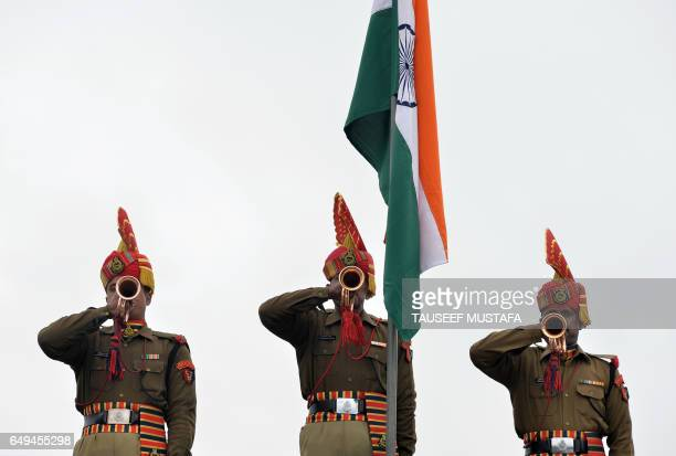 Indian Border Security Force soldiers blow trumpets during a passing out parade at BSF headquarter in Srinagar on March 8 2017 Some 126 new recruits...