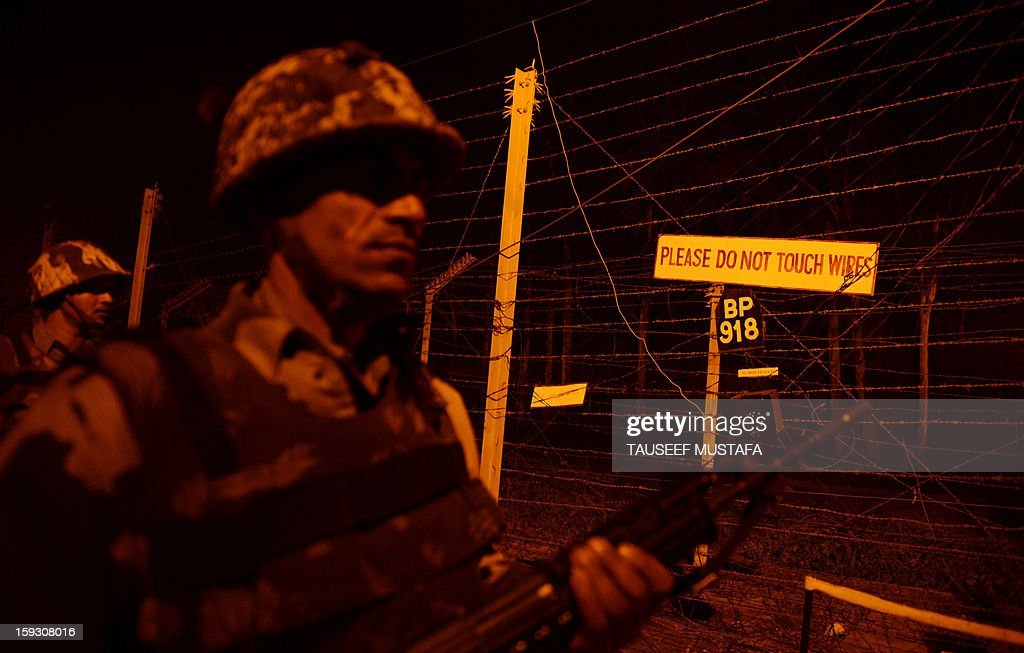 Indian Border Security Force (BSF) soldiers patrol along the border fence at an outpost along the India-Pakistan border in Suchit-Garh, 36 kms southwest of Jammu on January 11, 2013. Pakistan summoned the Indian ambassador to protest against 'unacceptable and unprovoked' attacks by the Indian army that killed two Pakistani soldiers in five days in Kashmir. AFP PHOTO/ Tauseef MUSTAFA