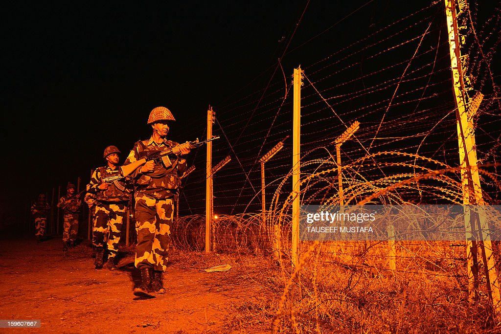 Indian Border Security Force (BSF) soldiers patrol along the border fence at an outpost along the India-Pakistan border in Abdulian, 38 kms southwest of Jammu, on January 17, 2013. A ceasefire took hold January 17 in disputed Kashmir after the Indian and Pakistani armies agreed to halt deadly cross-border firing that had threatened to unravel a fragile peace process. AFP PHOTO/Tauseef MUSTAFA