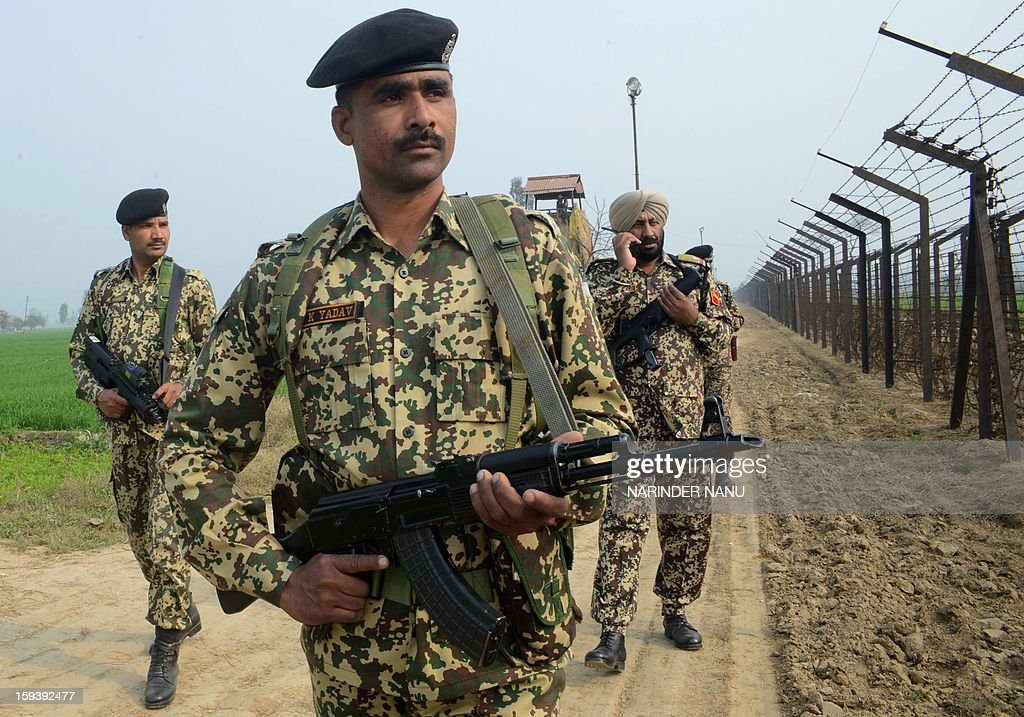 Indian Border Security Force soldiers patrol along the India-Pakistan border fence about 27 KM from Wagah on January 13, 2013. Two Indian soldiers died after a firefight erupted in disputed Kashmir on January 8, 2012 as a patrol moving in fog discovered Pakistani troops about 500 metres (yards) inside Indian territory, according to the Indian army.