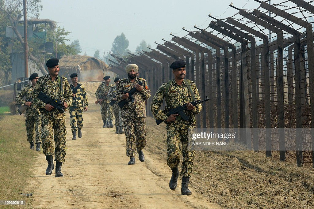 Indian Border Security Force soldiers patrol along the India-Pakistan border fence about 27 kms from Wagah on January 13, 2013. The beheading of an Indian soldier may have sparked a war of words between Delhi and Islamabad but the two nuclear rivals are both determined to prevent it from wrecking a fragile peace process. Two Indian soldiers died after a firefight erupted in disputed Kashmir on Tuesday as a patrol moving in fog discovered Pakistani troops about 500 metres (yards) inside Indian territory, according to the Indian army.