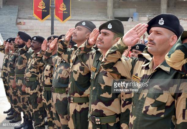 Indian Border Security Force soldiers salute during the flag hoisting ceremony on the occasion of India's 71st Independence Day at the IndiaPakistan...