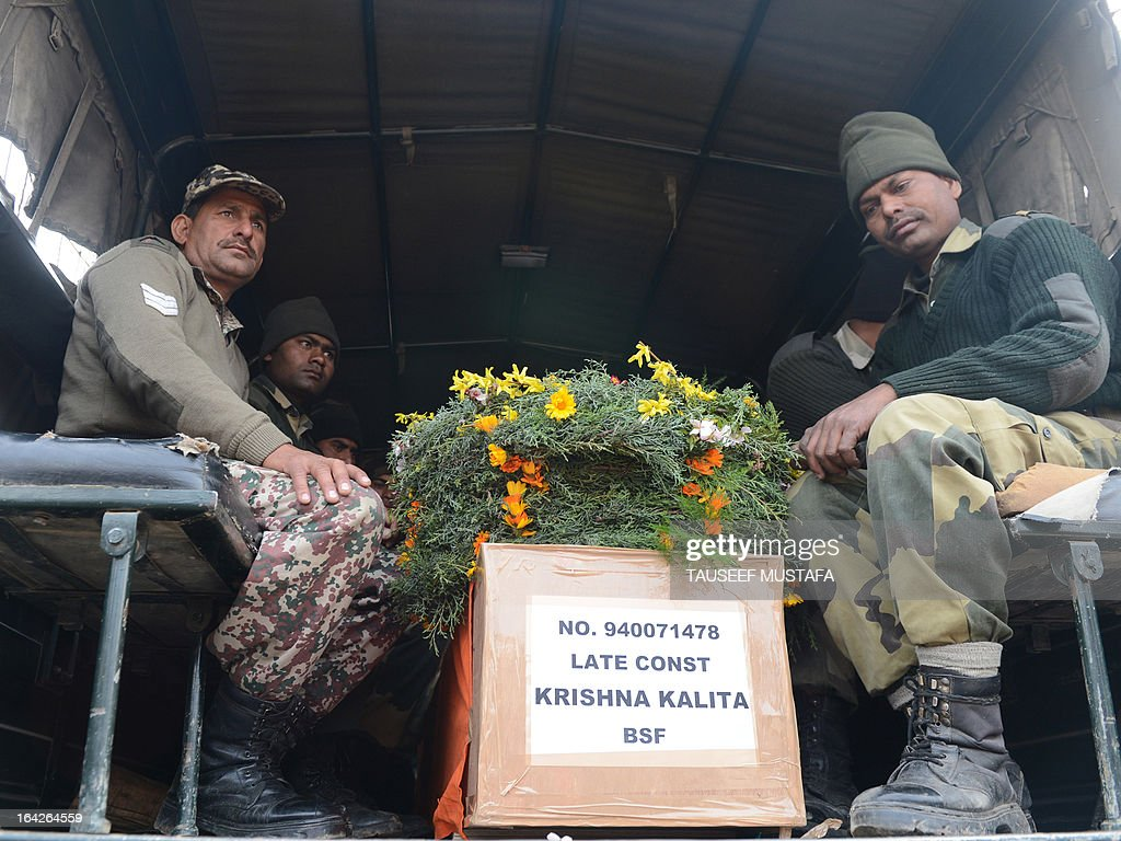 Indian Border Security Force soldiers sit in a truck with the coffin of a fallen comrade killed in yesterday's ambush in Srinagar on March 22 2013...