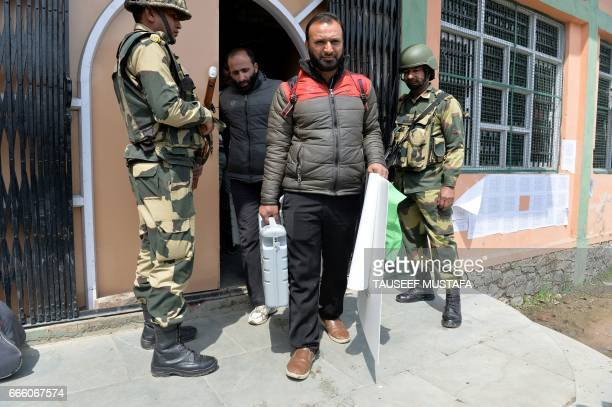 Indian Border Security Force soldiers stands guard outside a polling station as Kashmiri poll staff member collects voting machines in Srinagar on...