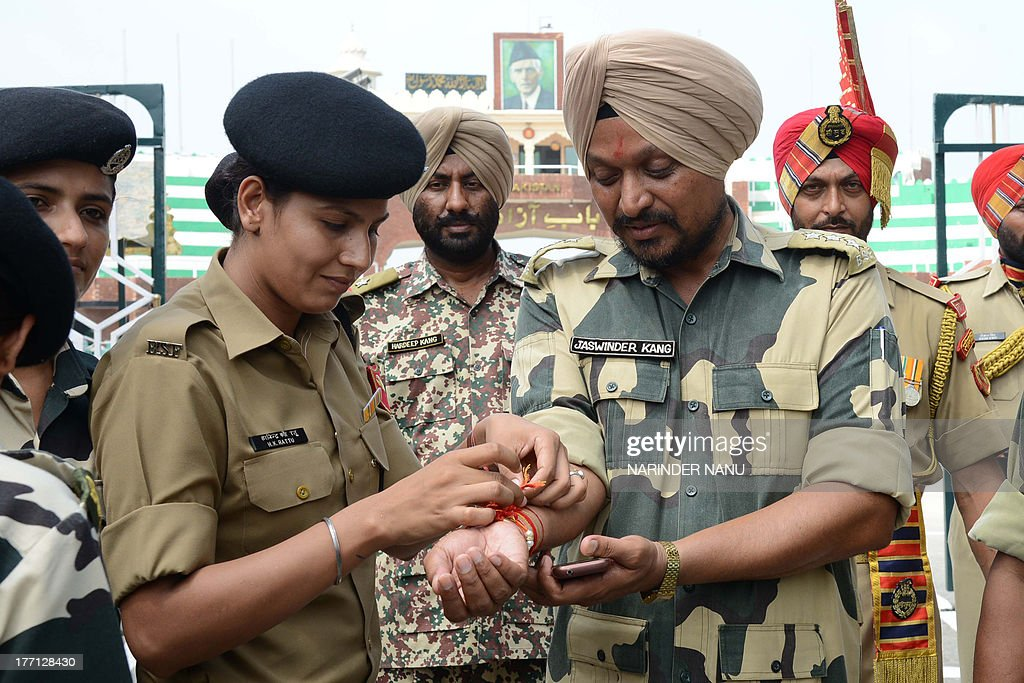 Indian Border Security Force (BSF) woman personnel ties a sacred thread or rakhi onto the wrist of Indian Border Security Force (BSF) Company Commander, Jaswinder Kang (R) during the Raksha Bandhan festival at the India-Pakistan Wagah Border post on August 21, 2013. The ceremony topically involves a bracelet being tied by a sister to her brother's wrist, symbolising the sister's love and prayers for her brother's well-being, and the brother's vow to protect her. AFP PHOTO/NARINDER NANU
