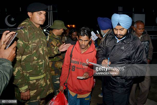 Indian Border Security Forces along with Immigration officials examine documents of an Indian fisherman as he crosses the IndiaPakistan border at...