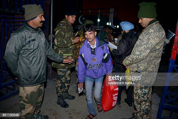 Indian Border Security Forces along with Immigration officials stand as an Indian fisherman crosses the IndiaPakistan border at Wagah some 35kms west...