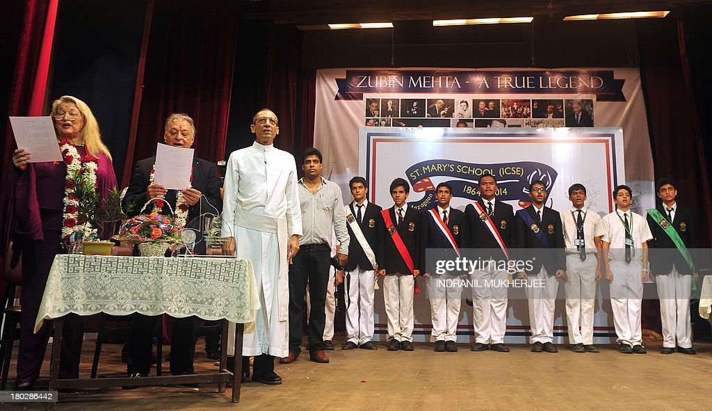 Indian born music conductor and composer Zubin Mehta (2L) and his wife Nancy Kovack (L) sing the school anthem during a visit to St. Mary's school, his alma mater, in Mumbai on September 11, 2013. Mehta led the Bavarian State Orchestra for a series of classical music concerts including one last week in the Mughal-era Shalimar Gardens on the banks of picturesque Dal Lake in conflict-scarred Kashmir's main city of Srinagar. AFP PHOTO/ Indranil MUKHERJEE