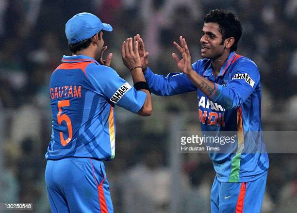 Indian bowler Manoj Tiwary celebrates with teammate Gautam Gambhir after taking his first International wicket of England batsman Tim Bresnan during...