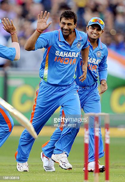 Indian bowler Praveen Kumar celebrates with teammates after dismissing Australian batsman David Warner in the their international T20 cricket match...