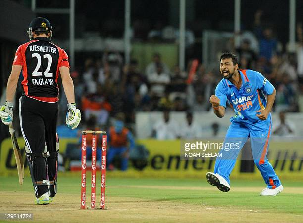 Indian bowler Praveen Kumar gestures as he celebrates the wicket of England batsman Craig Kieswetter during the first one day international cricket...