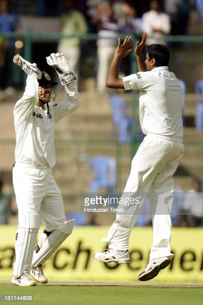 Indian bowler Ravichandran Ashwin celebrates with captain MS Dhoni after the dismissal of New Zealand batsman Kruger Van Wyk during third day of...