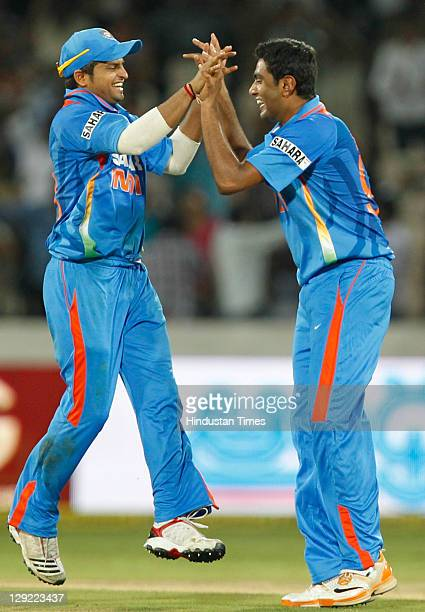 Indian bowler Ravichandran Ashwin celebrates with teammate Suresh Raina after taking the wicket of England player Ravi Bopara during the 1st One Day...
