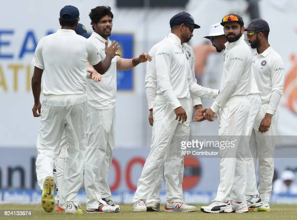 Indian bowler Umesh Yadav celebrates with his teammates after dismissing Sri Lankan batsman Danushka Gunathilaka during the fourth day of the first...