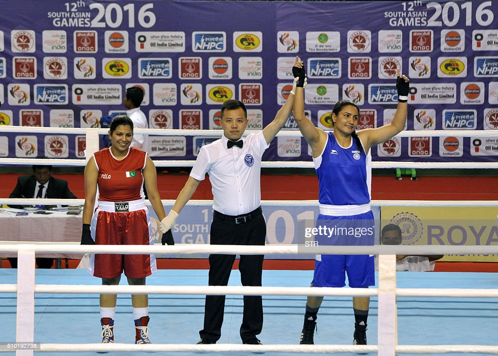 Indian boxer Pooja Rani (R) reacts after winning against Pakistan's Javed Sofiya (L) at the 12th South Asian Games 2016 in Shillong on February 14, 2016. Three Pakistani women are making history this weekend as they step into the boxing ring at the South Asian Games in India, the first time the conservative Muslim nation has fielded women boxers internationally. Khoushleem Bano, Rukhsana Parveen and Sofia Javed say to achieve their dream of competing they had to battle conservative groups in Pakistan who believe women should not participate in the sport. AFP PHOTO / STR / AFP / STR
