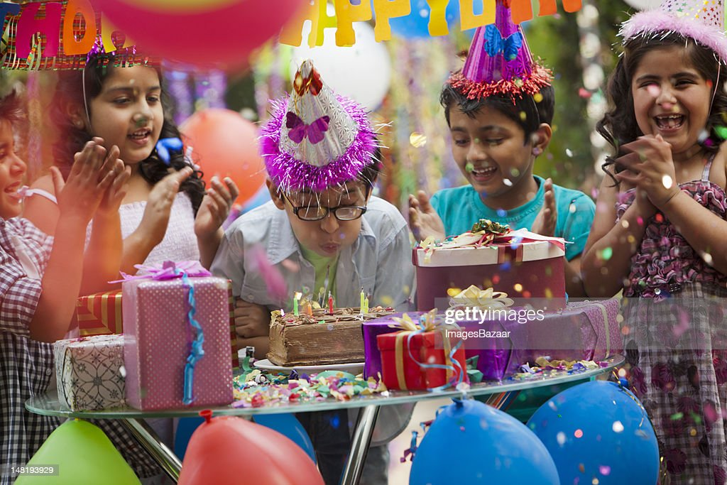 Indian boy (6-7) blowing out candles during birthday party : Foto stock