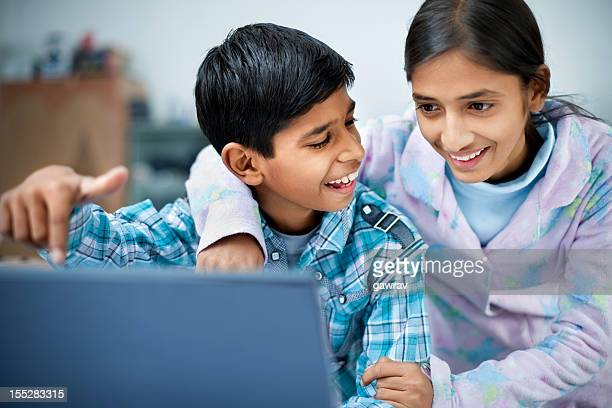 Indian boy showing something on laptop screen to elder sister
