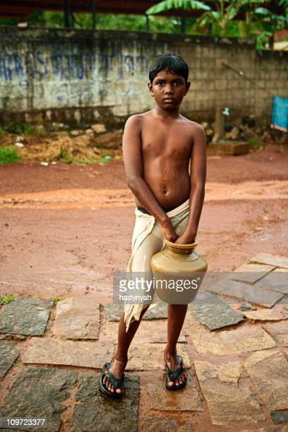 Indian boy standing in the pouring rain.