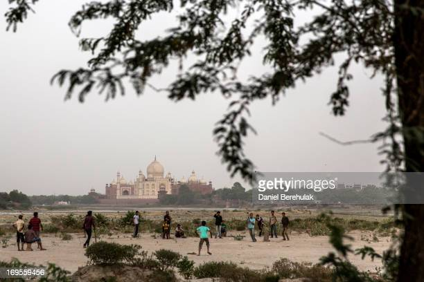 Indian boys play cricket in the banks of the Yamuna river as the Taj Mahal is seen in the distance on May 27 2013 in Agra India Completed in 1643 the...