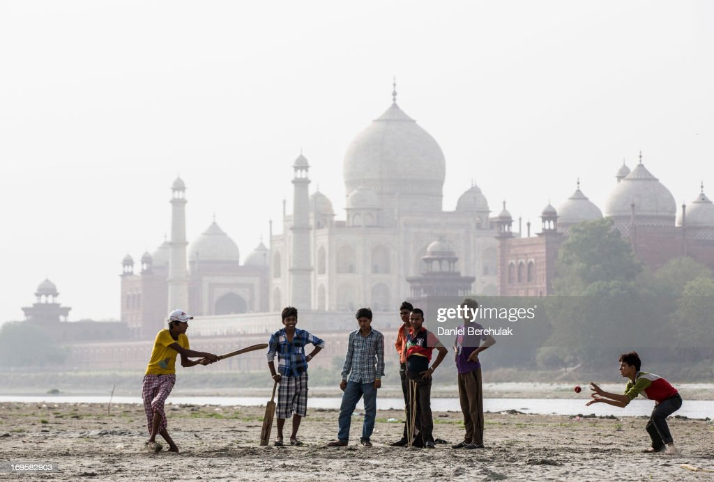 Indian boys play cricket on the banks of the Yamuna river as the Taj Mahal is seen in the distance on May 28, 2013 in Agra, India. Completed in 1643, the mausoleum was built by the Mughal emperor Shah Jahan in memory of his third wife, Mumtaz Mahal, who is buried there alongside Jahan.
