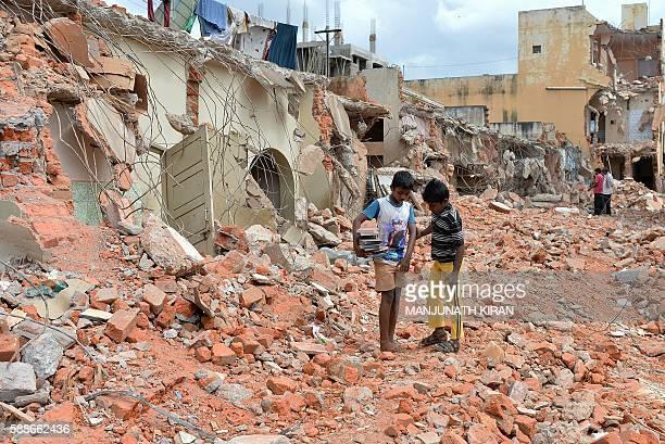 Indian boys salvage books amidst the debris of demolished houses a day after Bangalore's municipal authority Bruhat Bengaluru Mahanagara Palike...